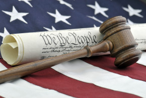 The US Constitution and a wooden judge's gavel all with an American flag background.